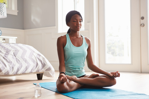 Young black woman doing yoga at home in