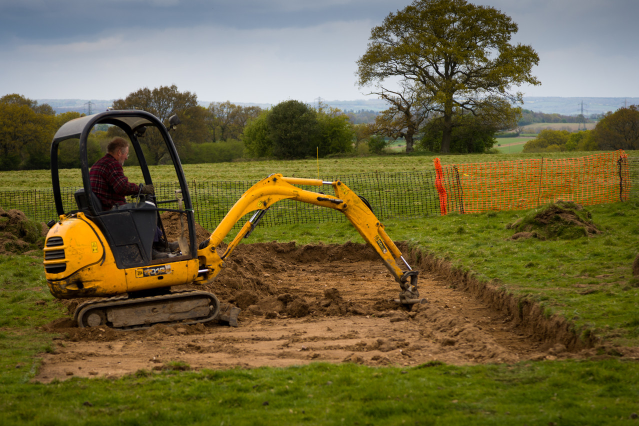 The mini-digger taking the turf and topsoil from Trench S