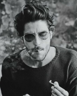 a man in sunglsses and with a cigarette