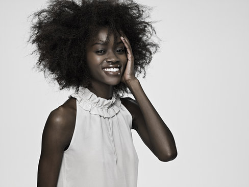 Modelling portfolio pictures: Lady with big natural hair and wonderful smile posing for the camera at our studio in Dubai.