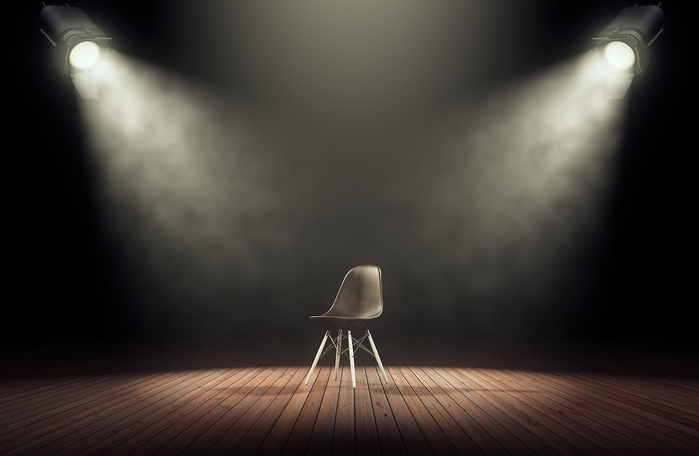 Two spotlights shine on an empty chair on a stage waiting for a stand up comic to start.