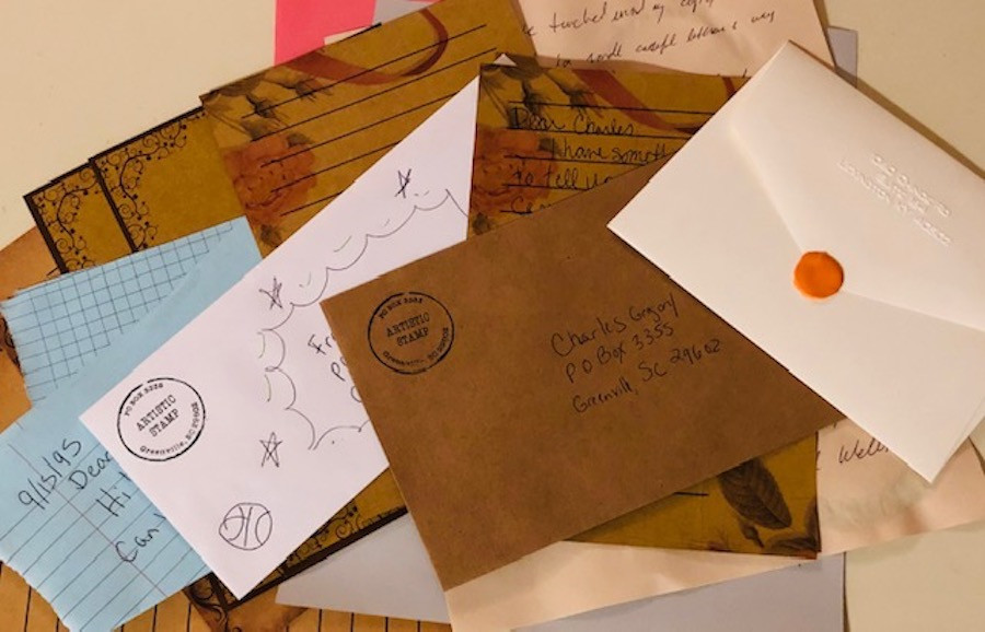 a stack of various color envelopes and paper with writing, orange wax seal