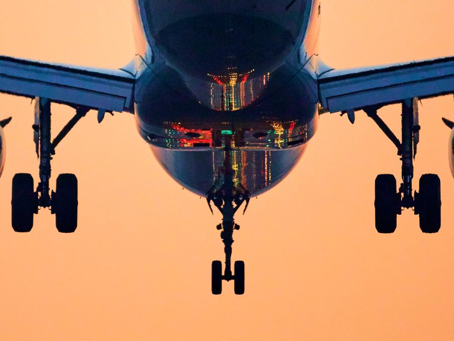 Ein Airbus A320 setzt zur Landung an. Im Rumpf spiegelt sich die Befeuerung der Landebahn.
