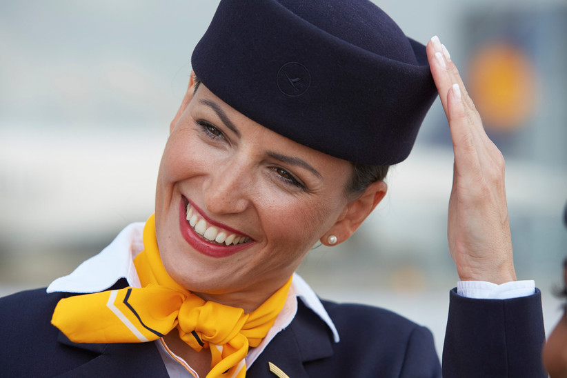Flugbegleiterin der Lufthansa hält ihre Pillbox, wie der Hut genannt wird.