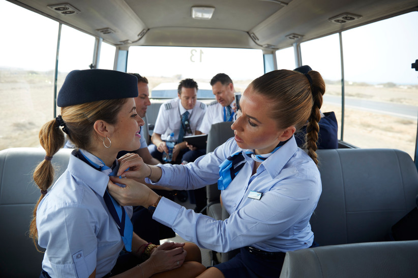 Im Crewbus auf dem Weg zum Flughafen wird die Uniform gerichtet.