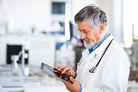 Senior doctor using his tablet computer