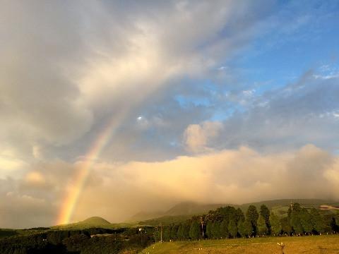 熊本県南阿蘇村で米塚を覆うようにかかる虹の写真