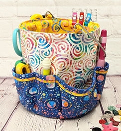 Caddy pop up container with a bucket handle in bright cotton fabrics filled with notions. Click to go to the product page for more information.