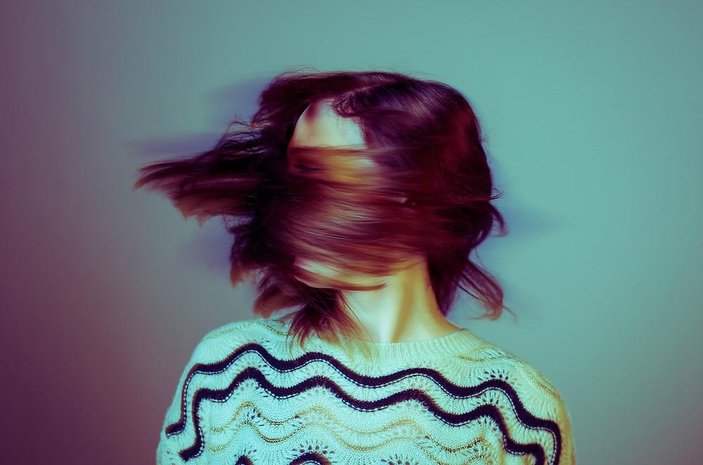 Mulher com o rosto tapado a sacudir o cabelo