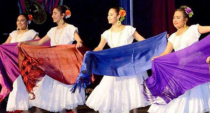 Folklórico dancers on stage in white dresses with colorful shawls.