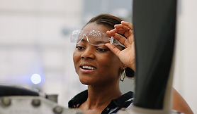 African American woman slightly raises goggles to look at equipment, smiling.