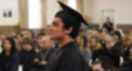 Male, adult learner in black cap and gown at graduation ceremony.