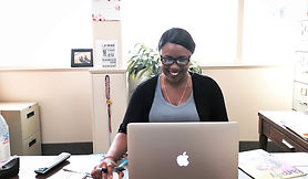 African American woman wearing glasses works at Apple computer and smiling