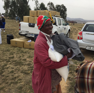 A very happy aid recepient with rice and blankets. Her smile says it all.