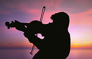 Violinist plays his heart out behind a sunset