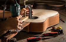 A luthier using  a router to channel th neck of a guitar for the placement of the truss rod