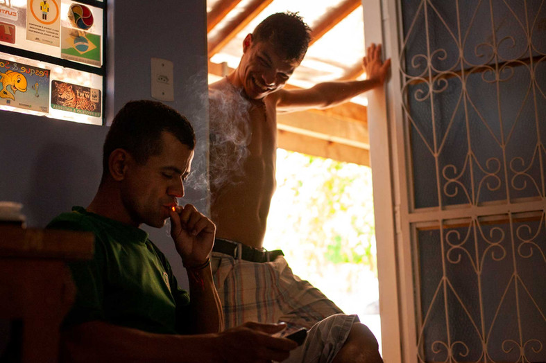 Nilson (Left) and Wender (right) take a smoke break during a work break. Both are construction workers and attenders to a local business in Cuiaba.