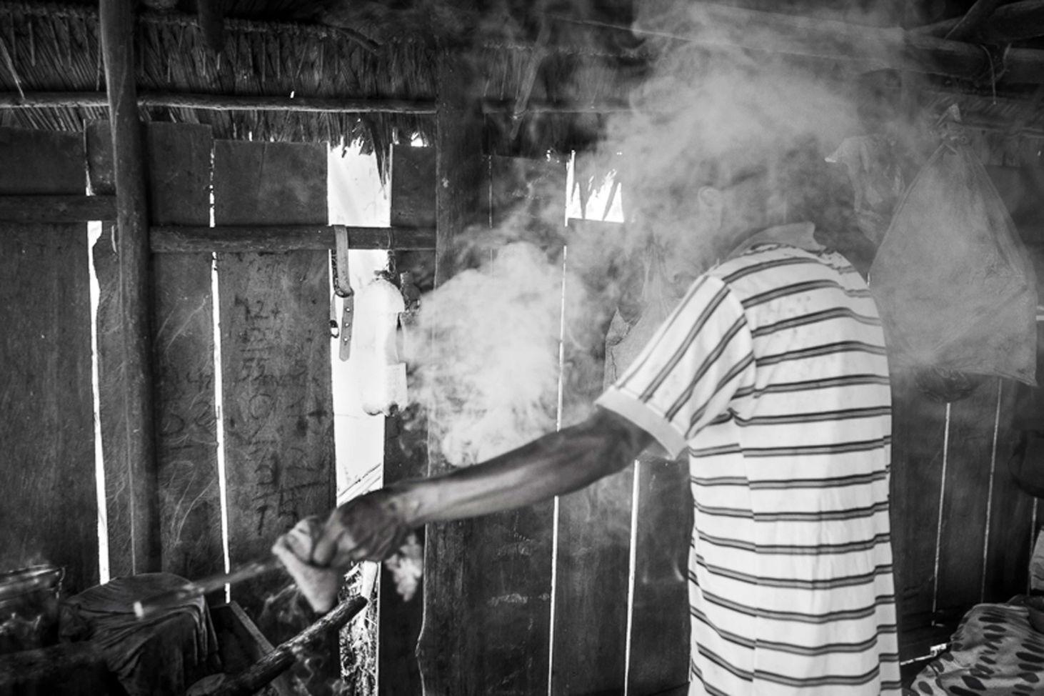 Man becomes engulfed with smoke while burning bamboo.