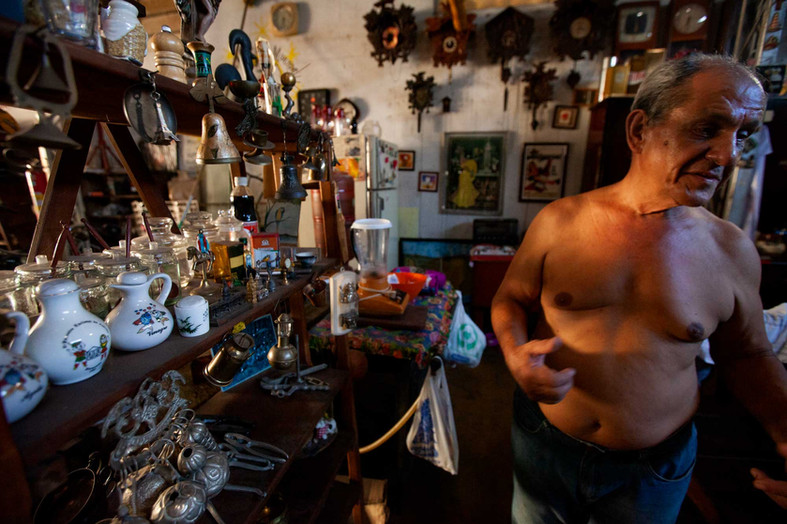 Cuibabá is often described as living in a hot frying pan. A man walks shirtless in his antique shop to counter the extreme heat in the city.