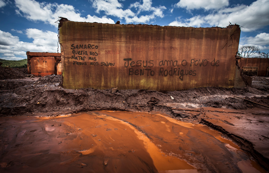 """An example of the Graffiti on an old school in Bento Rodrigues, """"Samarco wanted to kill us but Jesus saved us. Jesus loves the people of Bento Rodrigues."""""""
