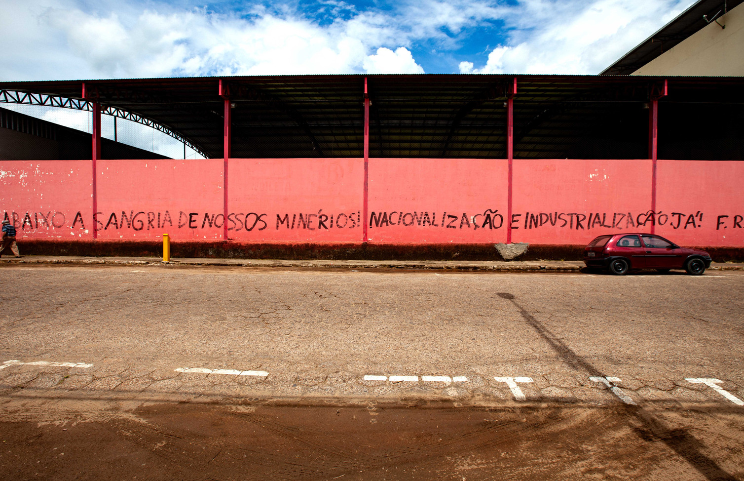 """A graffiti sign reads """"Under the blood of our miners! Nationalization and Industrialization"""". Mariana, Minas Gerais, BR."""