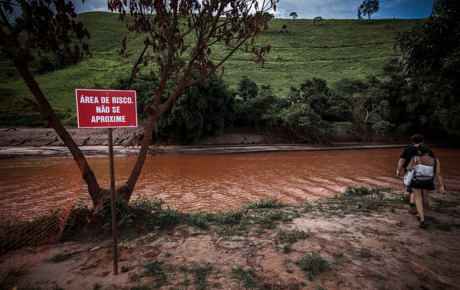 "After the disasterm, the river Rio Do Carmo, became contaminated with pollutants and waste. It's course spreads along from the Rio Doce into the Atlantic Ocean. A sign warns ""Area of risk; dont come close""."