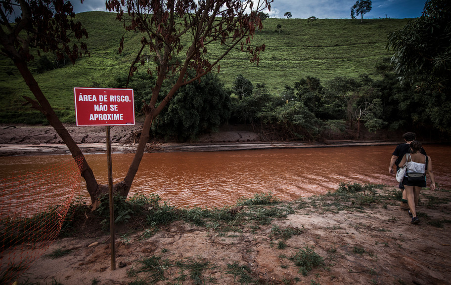 """After the disasterm, the river Rio Do Carmo, became contaminated with pollutants and waste. It's course spreads along from the Rio Doce into the Atlantic Ocean. A sign warns """"Area of risk; dont come close""""."""