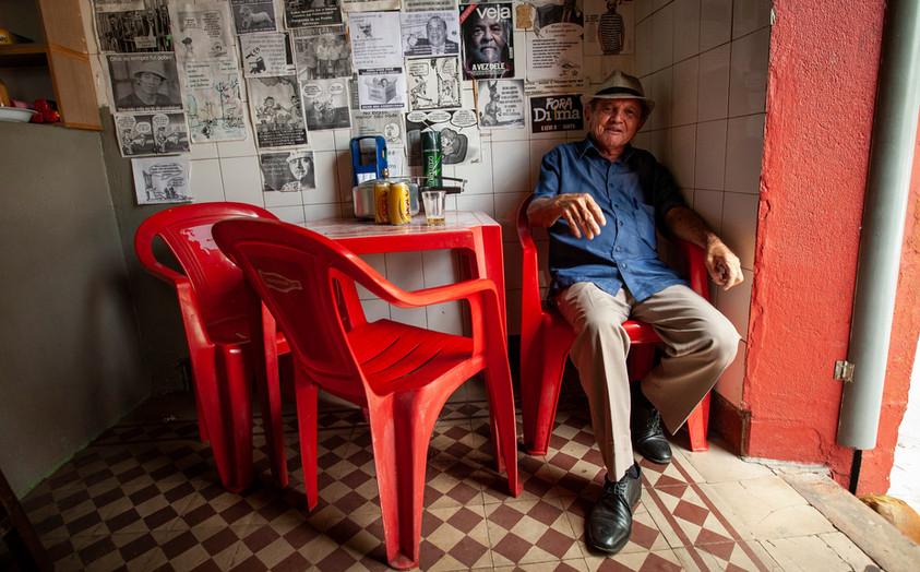 A man sits behind political propoganda in a bar. Cuiabá, Brazil.
