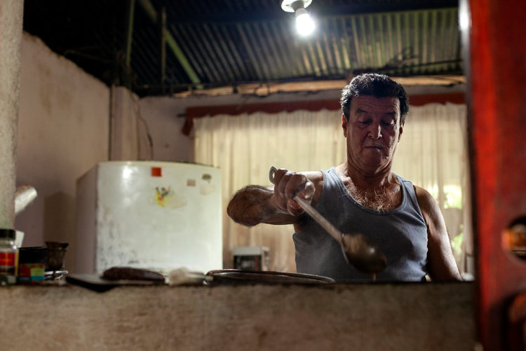 The whole family lived together under the same roof. Jefe (cheif, father) prepares morning breakfast for the family which includes rice and beans.