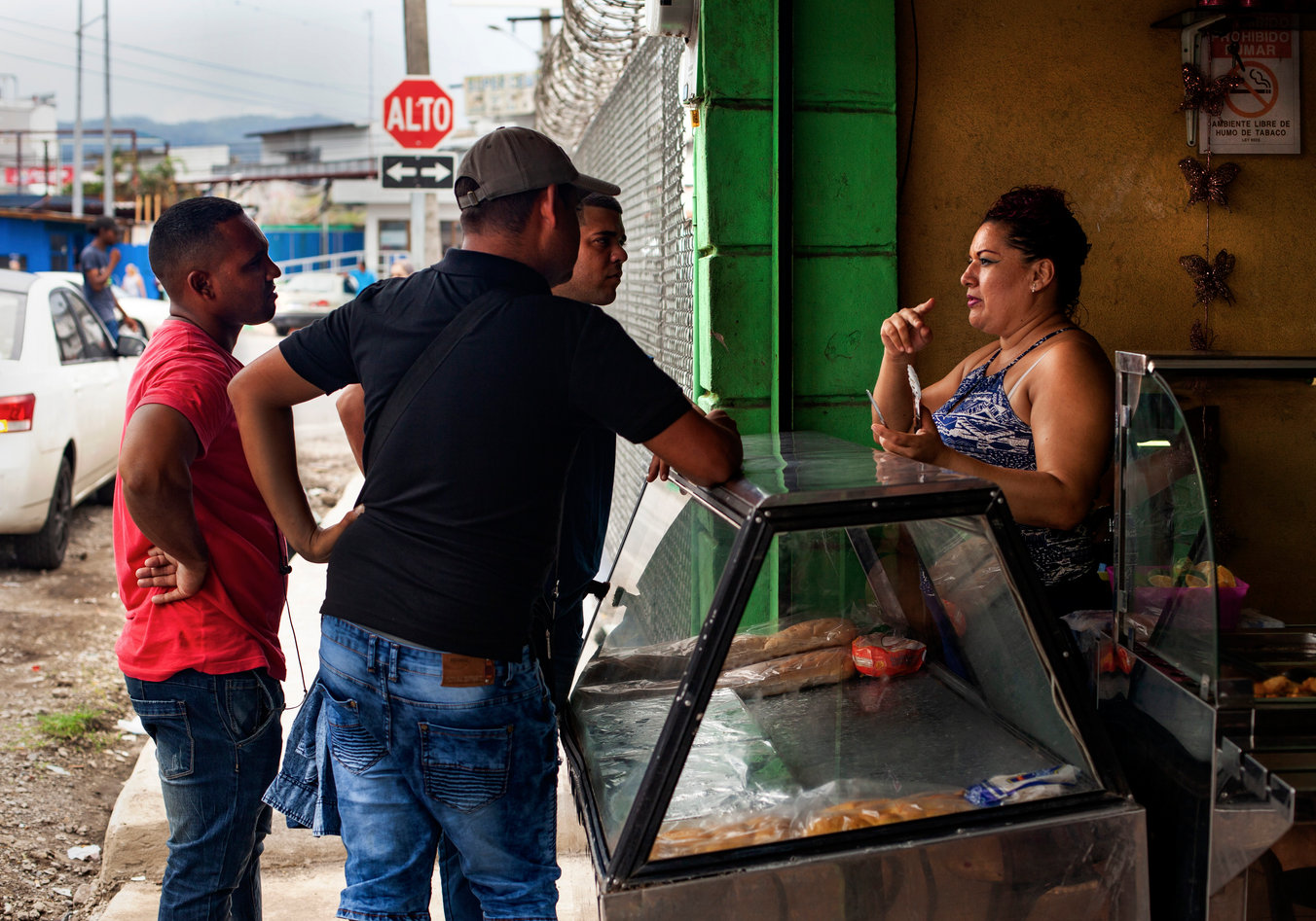 Yolanda, the owner of a meat store on the border, gives directions to the nearest bank to migrants passing through.
