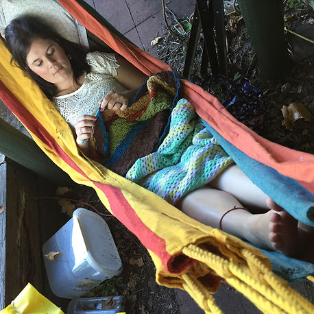 Lilybily Designs creator crocheting in a hammock