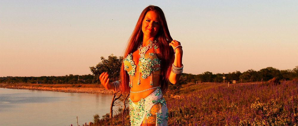 Magdansös i Stockholm i ljusblå och vit magdansdräkt på stranden vid solnedgången.