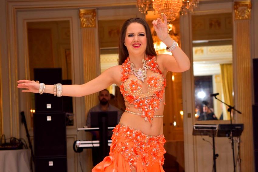 Maja Magdans dansar på ett bröllop i Stockholm i orange magdansdräkt.