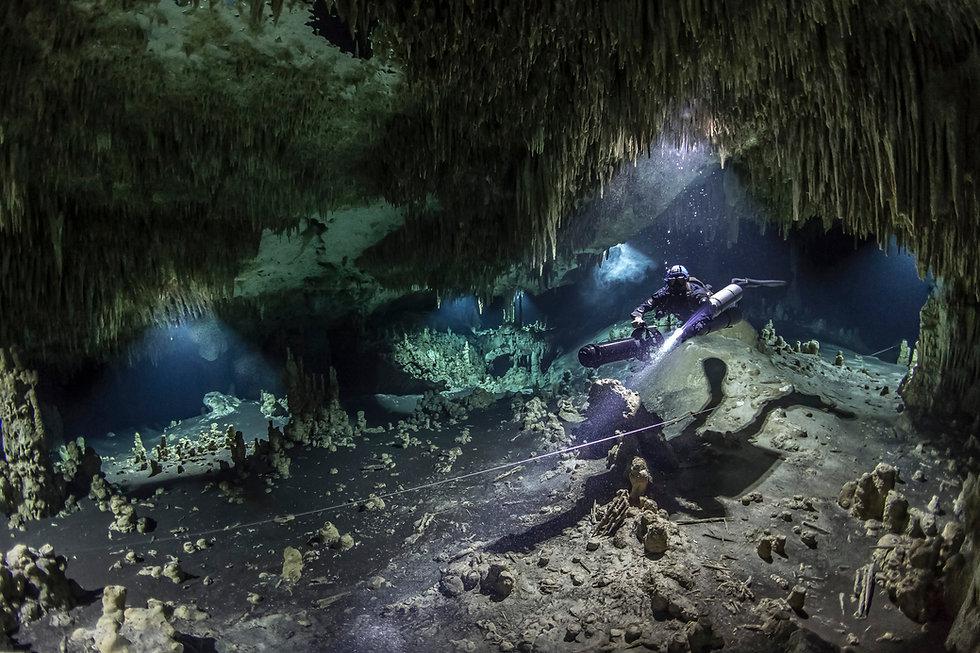 A DPV cave diver swims in the Hatzuts Ak