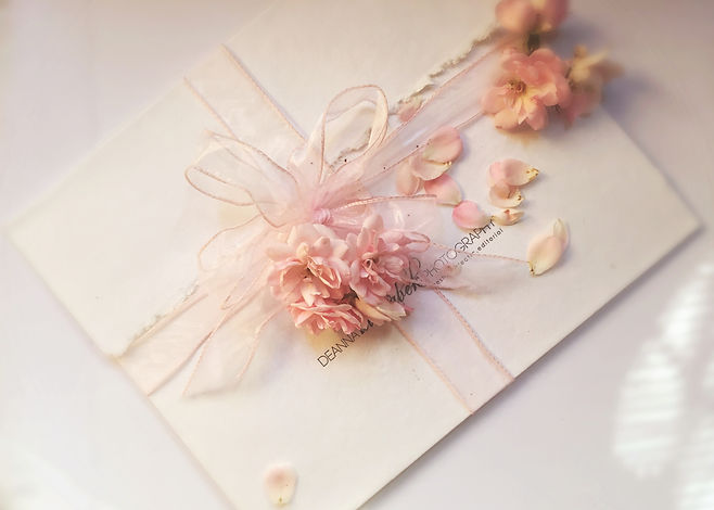 Whie envelope with white ribbon and pink flowers.