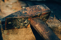 Old rusty hammer on wood