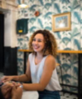 laughing gimixed race, friends, eurasian, eurasian girl, curly hair, singapore, singaporean, white top, jeans, cafe, smiling