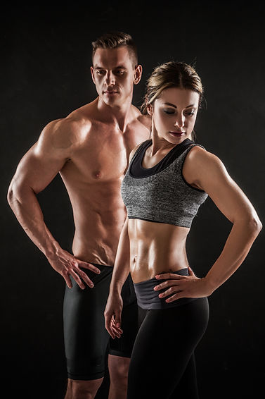 Sporty young couple with dumbbells on bl