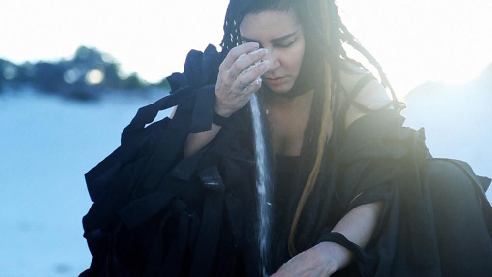 Artista Rebeca Matta vestida de preto joga areia no meio de uma duna.
