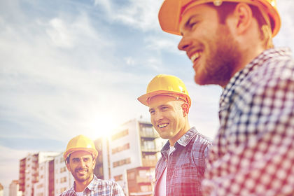 business, building, teamwork and people concept - group of smiling builders in hardhats at construct