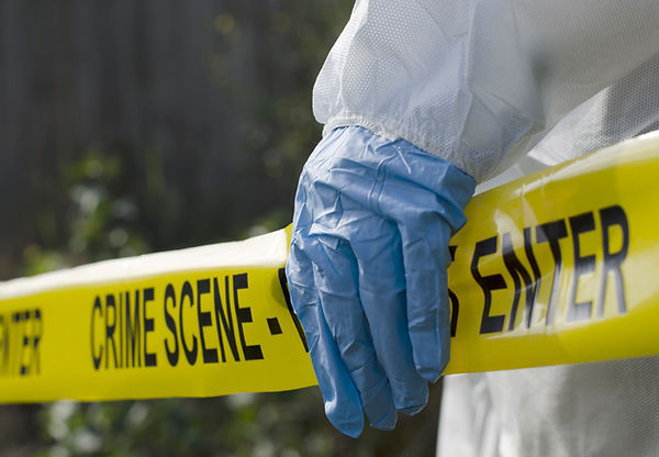Crime scene tape held by worker in biohazard suit