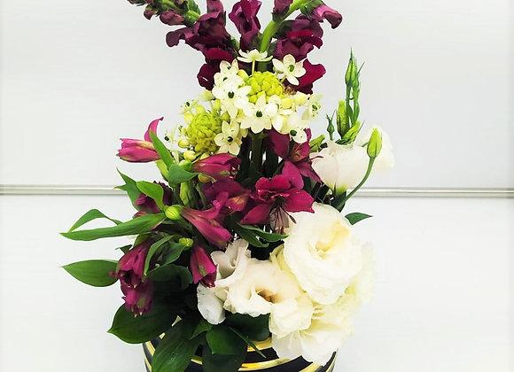 שזירת פרחים חיים באגרטל כדורי בצבעי זהב ושחור.
