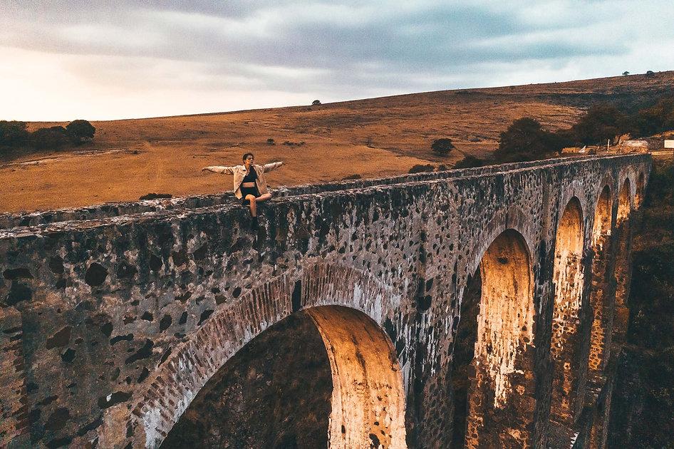 Девушка сидит на мосту Arcos del Sitio