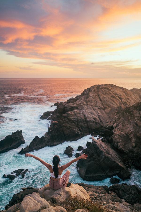 Девушка сидит на обрыве берега Тихого океана на закате