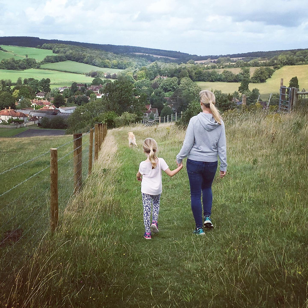 Sussex days out - mother and child hand in hand walking in countryside