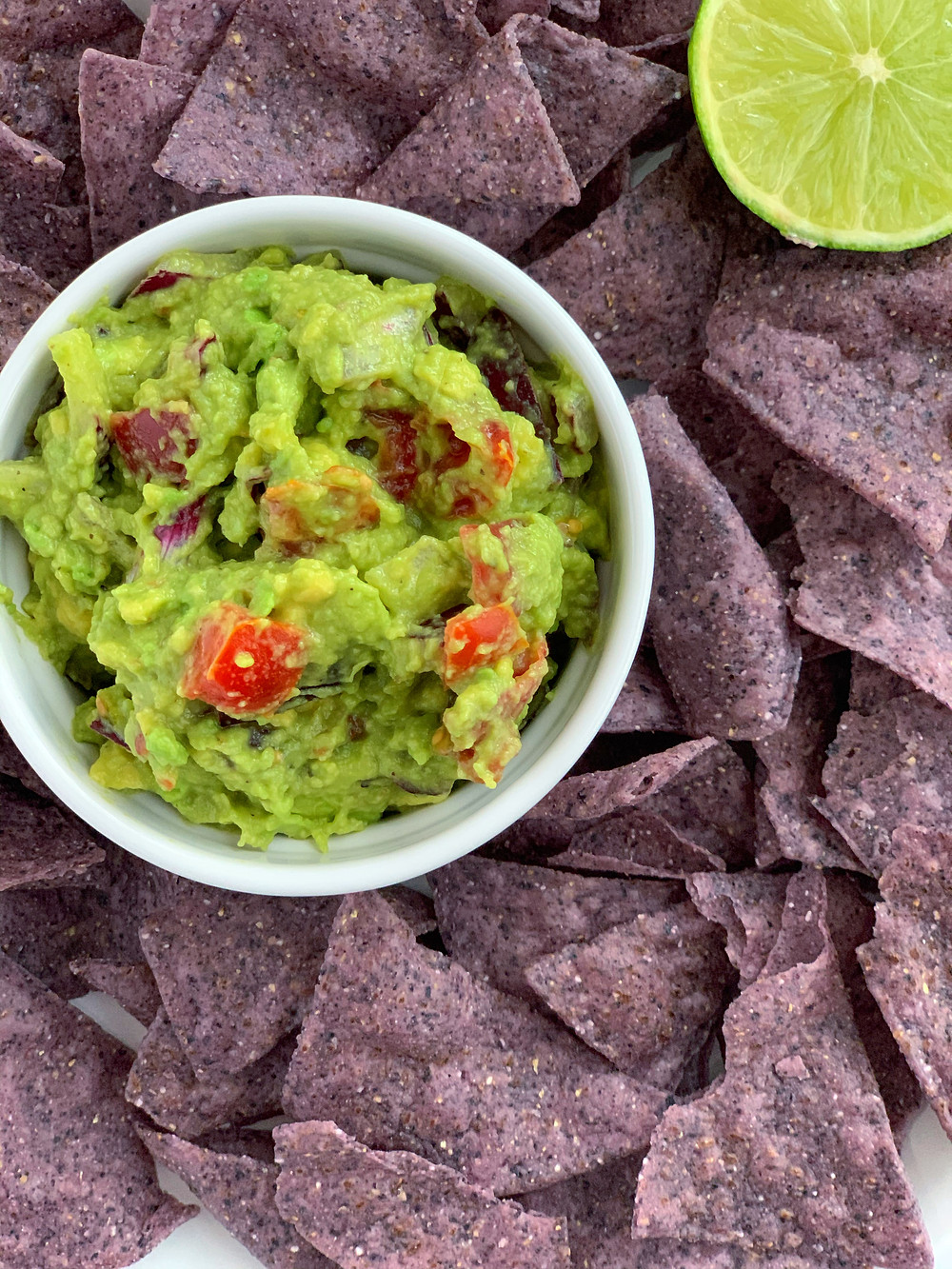 overhead shot of creamy 5-minute guacamole and blue tortilla chips with a lime