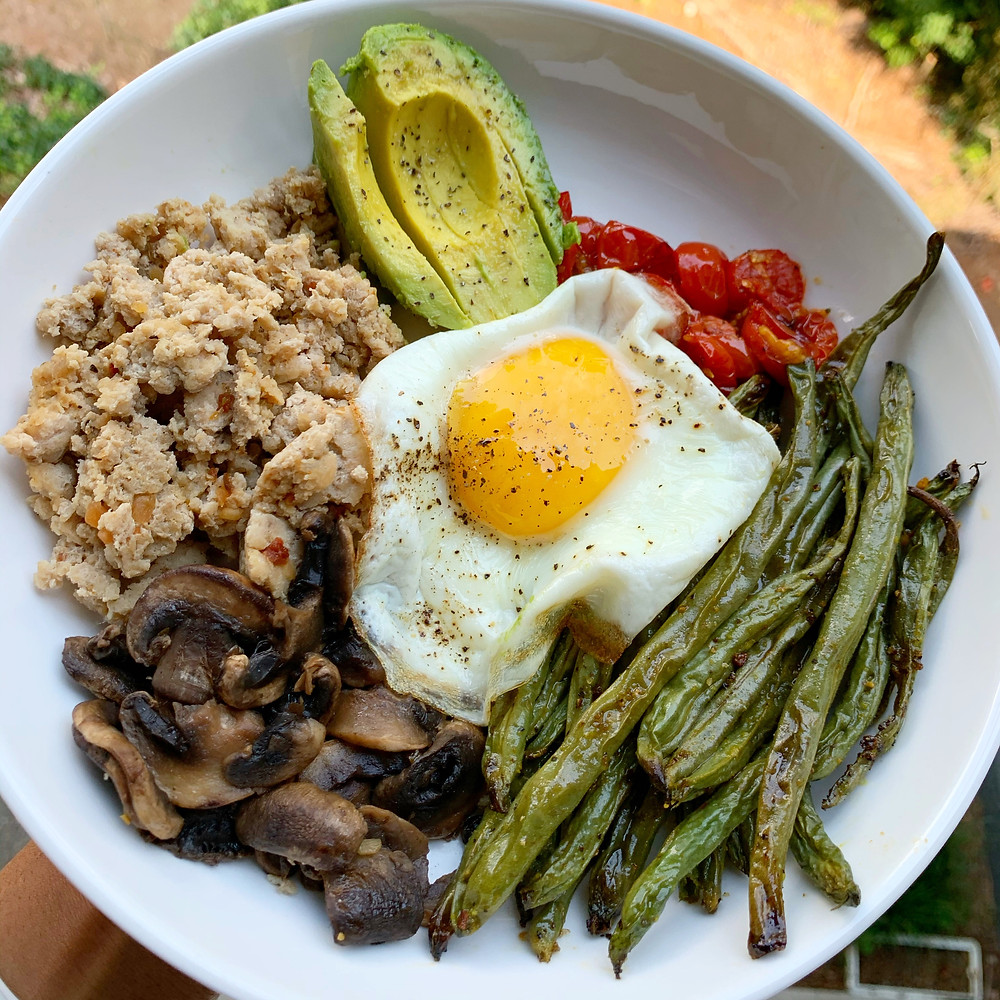 overhead shot of burger bowl with ground chicken, avocado, mushrooms, tomatoes, green beans, and fried egg