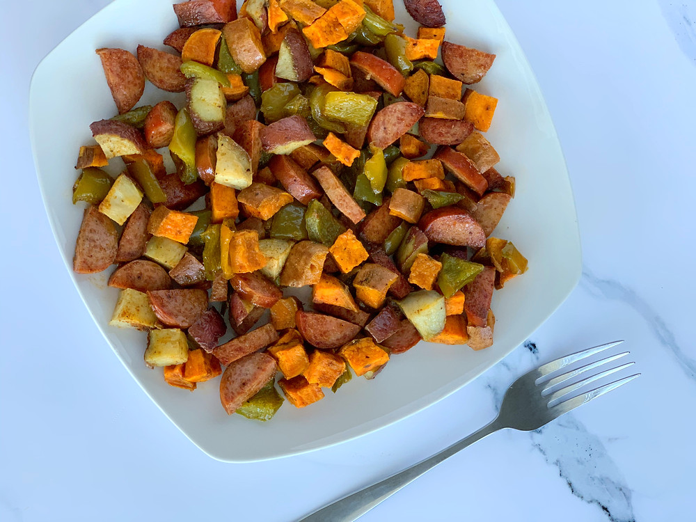 overhead shot of sheet pan sausage and veggies with sweet potatoes, green bell peppers, red potatoes, and turkey sausage