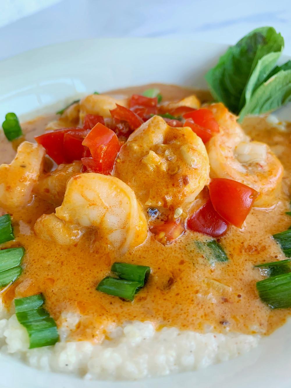 closeup shot of cajun shrimp and grits with tomato sauce