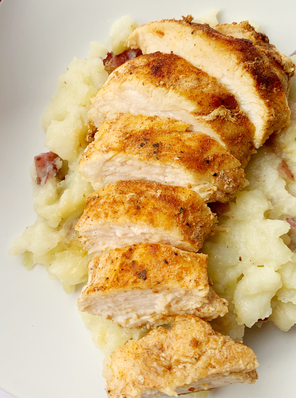 closeup shot of sliced juicy jerk chicken breasts over a mound ofgarlic mashed red potatoes